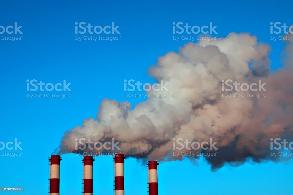 Four smokestacks of a thermal power station with clouds of smoke, air steam and blue sky in a winter day. vector art illustration