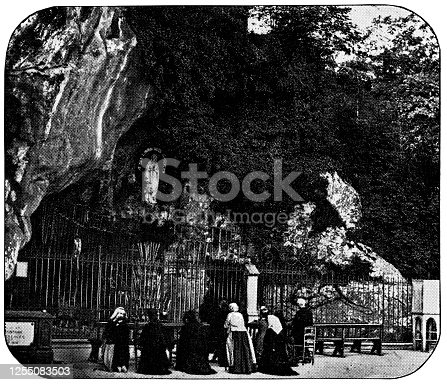 Grotto of Massabielle at the Sanctuary of Our Lady of Lourdes in the town of Lourdes in the Pyrenees Mountains in France. Vintage half tone etching circa 19th century.