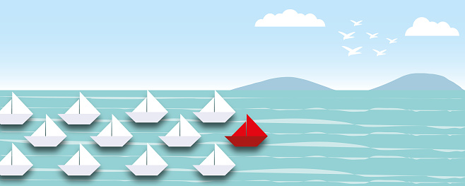 Group of white boats followed the red boat in the sea with sky background as metaphor for Business target.