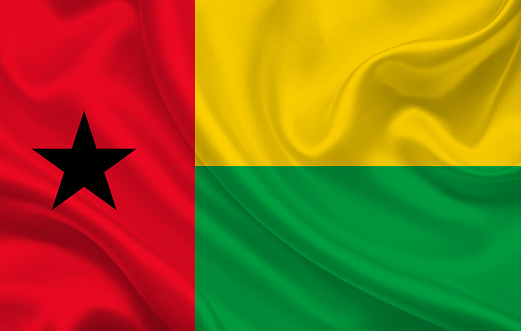 Guinea-Bissau country flag on wavy silk fabric background panorama