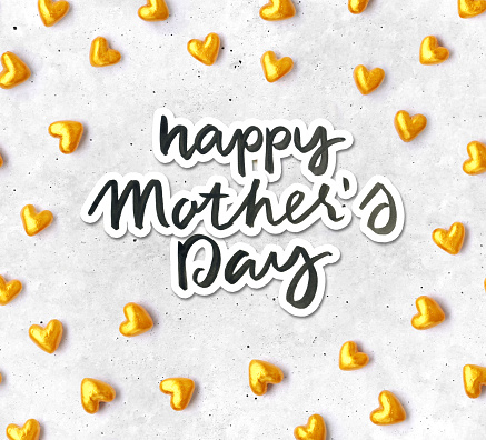 Hand-made composition of gold and red hearts with handwritten text HAPPY MOTHERS DAY - beautiful original love card design