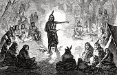 istock Indians council meeting, chief standing in the middle, arm outstretched 1255372889
