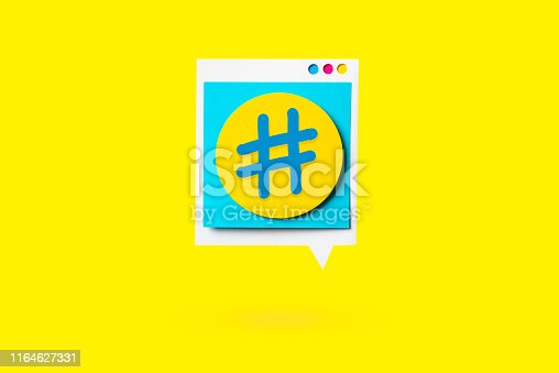 Isolated paper cutout of hashtag symbol on a yellow speech bubble on yellow background. Concept of social media and digital marketing.