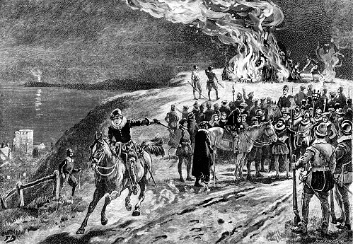 """The lighting of one in a chain of warning beacons to alert the populace that the Spanish Armada has been sighted off the South Coast in a planned invasion of England. Another beacon fire can be seen on the horizon. From """"The Sunday at Home: A Family Magazine for Sabbath Reading, 1888"""". Published in London by the Religious Tract Society."""