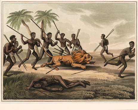 Vintage illustration features Native Africans with spears surrounding a lion. An injured man lies in the foreground.