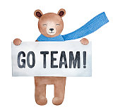 Little cheerful teddy bear character holding big paper sign board with written inscription 'Go Team!'.