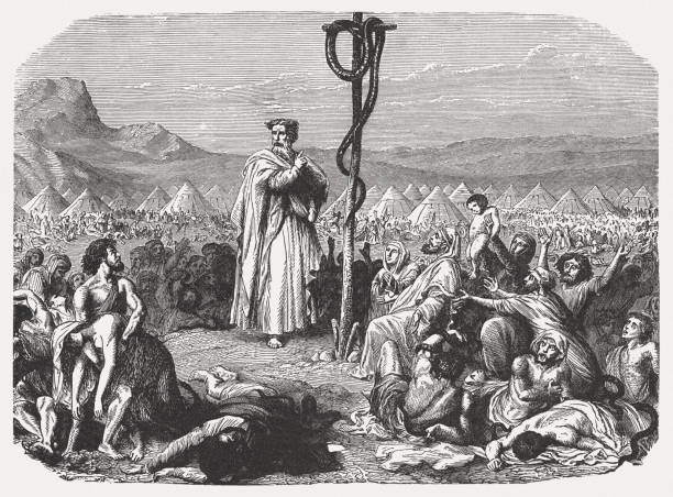 Moses and the serpent of brass (Numbers 21, 9) And Moses made a serpent of brass, and put it upon a pole, and it came to pass, that if a serpent has bitten any man, when he beheld the serpent of brass, he lived (Numbers 21, 9). Wood engraving, published in 1886. moses religious figure stock illustrations