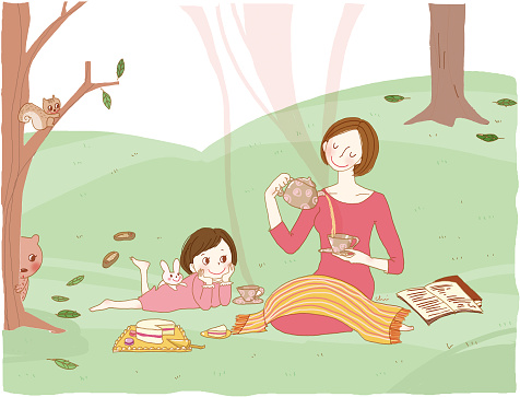 Mother and daughter having tea in the field.