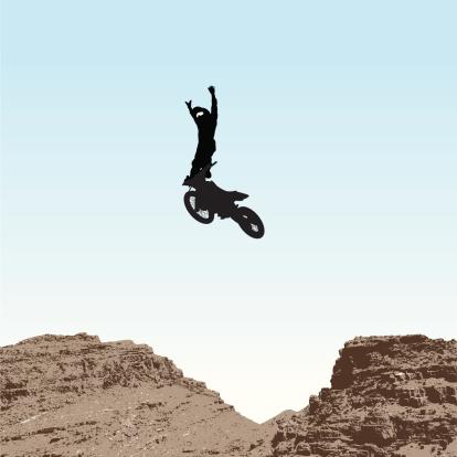 Motocross rider going off jump in the high dessert