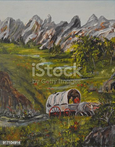 An ox drawn covered wagon traverses through the mountains.