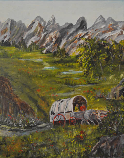 Oregon Trail An ox drawn covered wagon traverses through the mountains. 20th century history stock illustrations