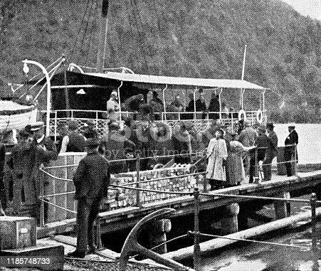 Passengers boarding the PS Skibladner paddle steamer boat on Mjosa lake in Norway. Vintage halftone etching circa late 19th century.