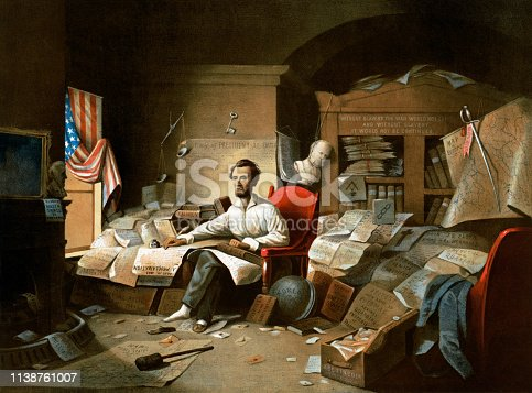 Vintage image depicts Abraham Lincoln writing the Emancipation Proclamation. In a cluttered study, Lincoln sits in his pajamas at work on the document, his hand resting on the Bible and the Constitution.