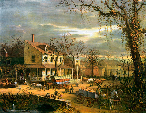 Vintage illustration features a busy autumn American scene outside an inn at a crossroads. In the lower right, a man drives a cart hauling slaughtered pigs; at center is a conestoga wagon in front of the inn.