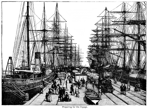 Sailing ships, passengers and cargo at a busy pier