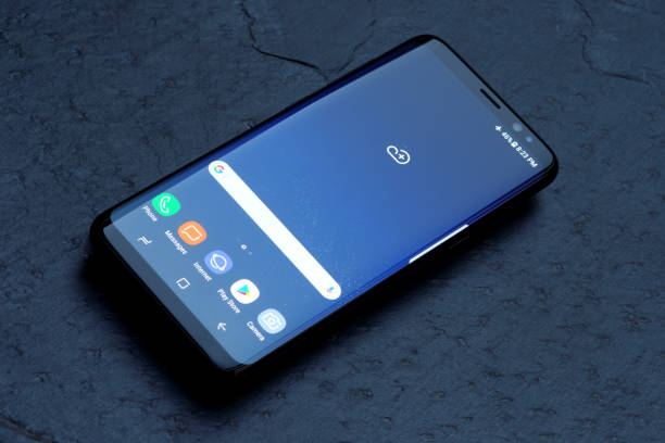 Samsung Galaxy S8 Koszalin, Poland – 25 April, 2017: Black Samsung Galaxy S8 on stone table. Samsung S8 are new generation smartphone from Samsung. The Samsung S8 is smart phone with multi touch screen brand name stock illustrations