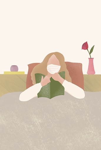 A sick women wearing a medical face mask and reading a book