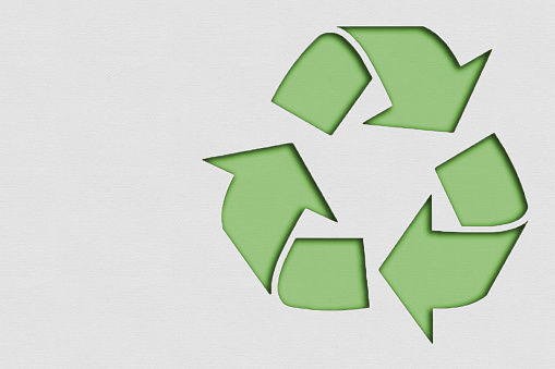 Symbol of recycled material made with paper on cardboard