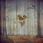 The little boy and brown pelican fly  in the autumn forest
