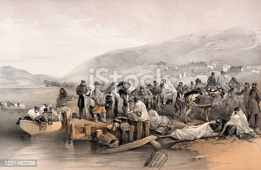 Vintage image shows hundreds of sick and wounded at the harbor in Balaklava, Sevastopol on the Crimean Peninsula during the Crimean War (1853-1856.) They would be boarded onto small, open boats to be transferred to larger ships and taken to the hospital at Scutari in Istanbul.