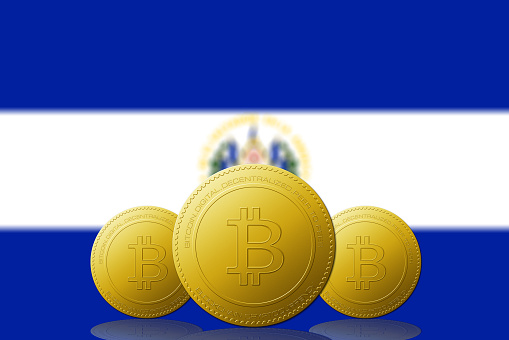 Three Bitcoins cryptocurrency with El Salvador flag on background.