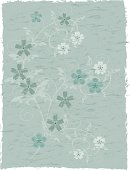 A piece of old worn and torn fabric or wallpaper with a floral design.