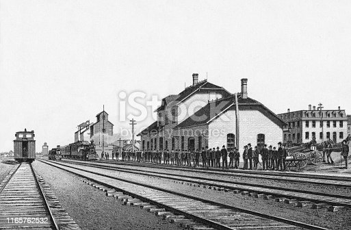 Row of people at the train station in Brandon, Manitoba, Canada. Vintage etching circa late 19th century.