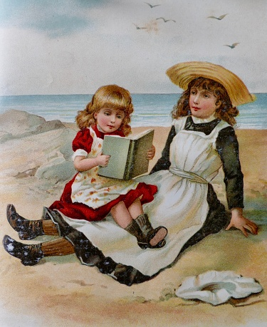 Two girls sitting on beach reading a book