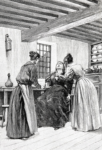 Two women in the kitchen help another woman who has a weakness