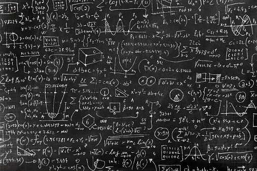 Complicated math formula, full of symbols, drawings, numbers, variables and equations written on a blackboard with white chalk.