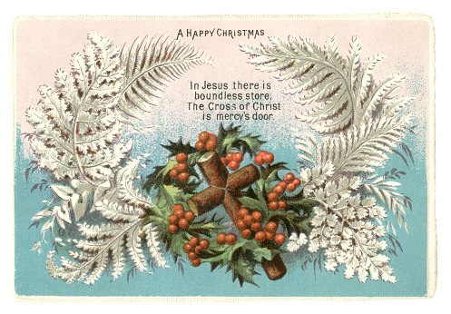 """A Victorian Christmas card from 1874 showing a wooden cross surrounded by holly leaves and berries with silver coloured ferns. A verse proclaims, """"In Jesus there is boundless store, The Cross of Christ is mercy's door""""."""