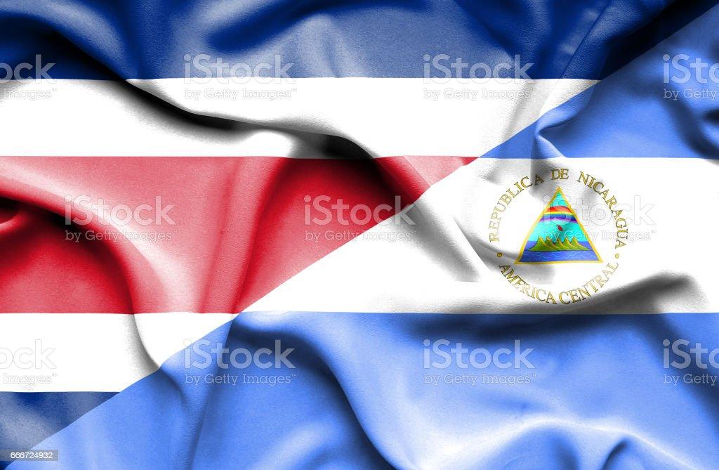 Waving flag of Nicaragua and Costa Rica - ilustração de arte em vetor
