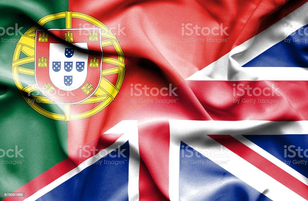 Waving flag of United Kingdon and Portugal - ilustração de arte vetorial