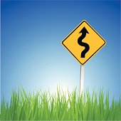 Road sign with a winding road standing in a grassy field