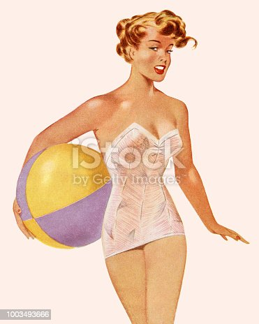 istock Woman in Bathing Suit Holding a Beach Ball 1003493666