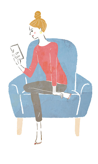 A woman touching her cellphone on the sofa