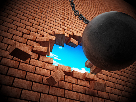 Wrecking ball demolishing brick wall