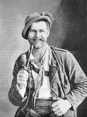 Young man in traditional Bavarian costume with pipe, portrait, sitting, smiling, happy