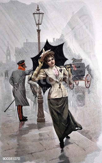 istock Young woman walks on the street with umbrella in the rain - 1896 900581070