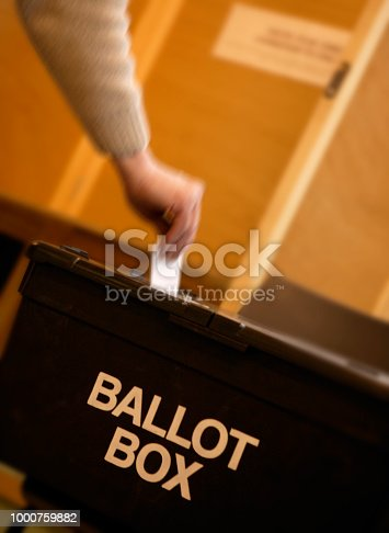 HAND PLACING VOTING SLIP INTO BLACK BALLOT BOX IN CLOSE UP