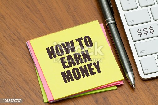 HOW TO EARN MONEY written on STICKY NOTE NEAR computer keyboard.