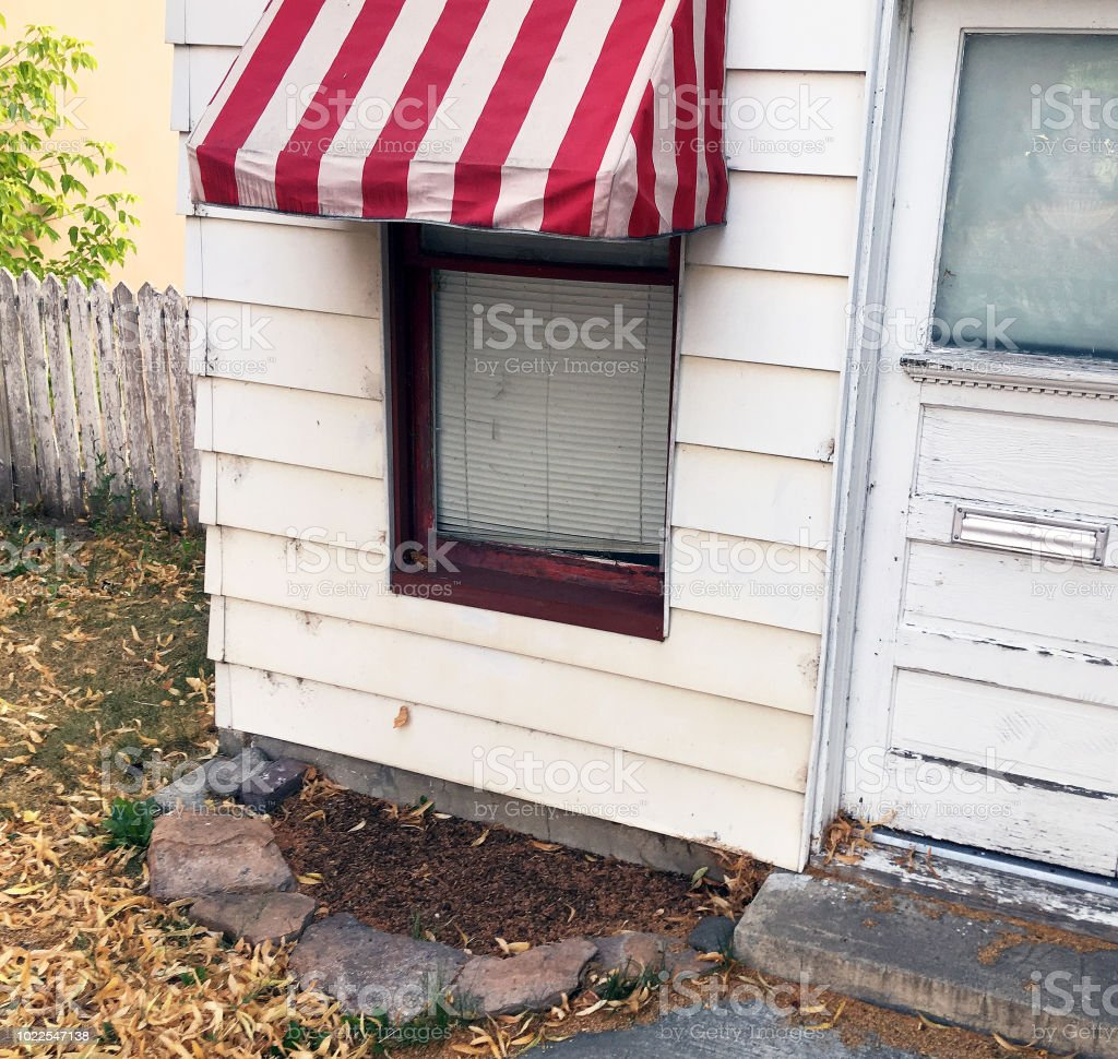 WINDOW WITH STRIPED AWNING stock photo