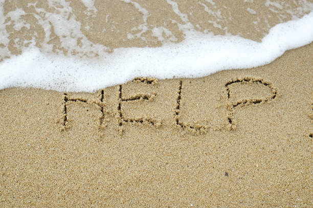 HELP The word HELP written on sand being washed away by wave suicide stock pictures, royalty-free photos & images