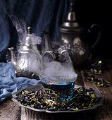 синий тайский чай из лепестков цветов в серебряной чашке