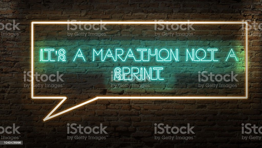 IT IS A MARATHON NOT A RACE NEON SIGN ON A BRICK WALL DARK WITH TEXT BUBBLE SYMBOL stock photo