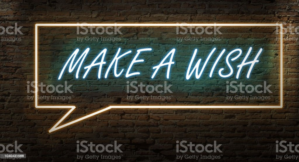MAKE A WISH NEON SIGN ON A DARK ALLEY WALL NIGHT stock photo