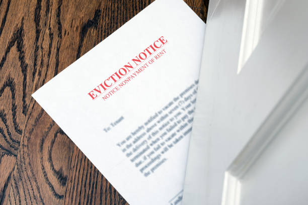 EVICTION NOTICE ON HARDWOOD FLOOR SLIPPED UNDER ENTRANCE DOOR Eviction Notice information sign stock pictures, royalty-free photos & images