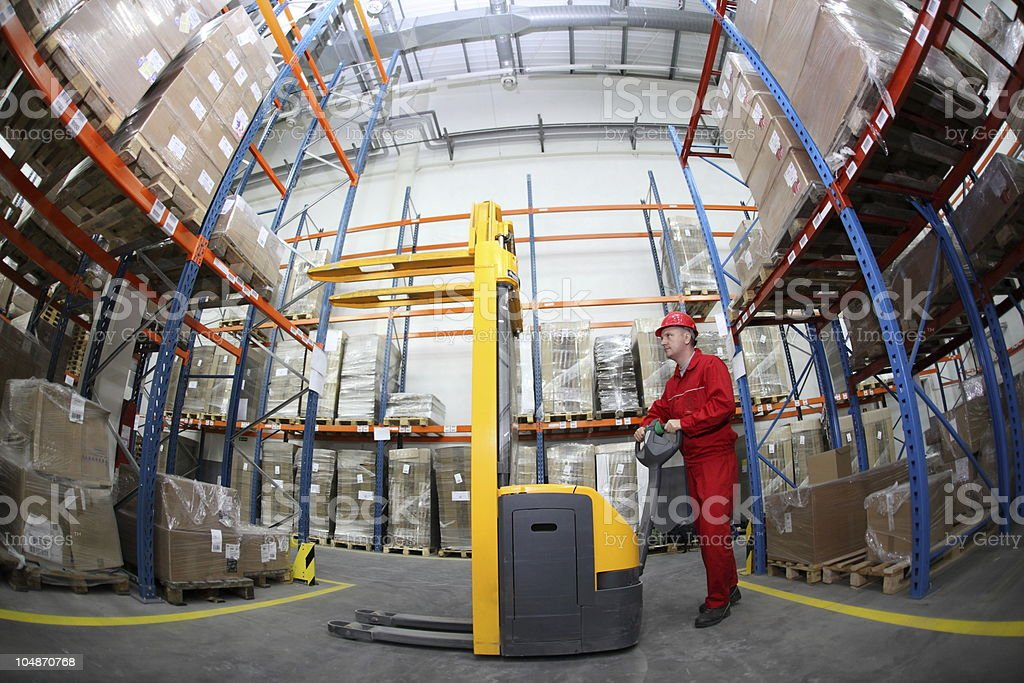 MANUAL FORKLIFT OPERATOR AT WORK IN WAREHOUSE royalty-free stock photo
