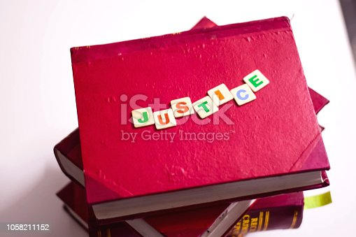 JUSTICE WRITTEN ON RED LAW BOOKS WITH COLORFUL BLOCK LETTERS INDICATES LAW STUDY , COURT , LAWYER , JUDGEMENT , LAWSUIT , LAW EDUCATION