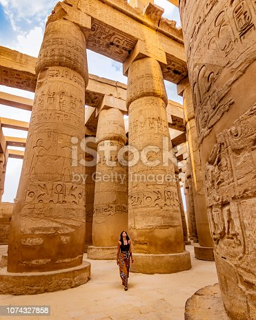 Young female traveller wandering through ancient Karnak Temple. Beautiful Egyptian landmark with hieroglyphics. Travelling woman adventuring around the world. Luxor, Egypt